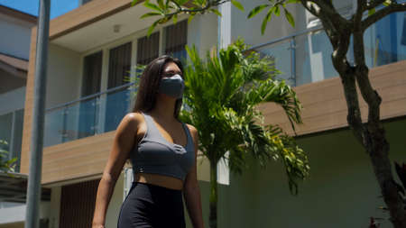 A young European brunette sports girl walks along an empty city street with green trees on the background alone in a gray protective mask on her face Imagens