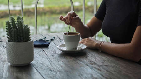 A young European girl sits at a table in a public place with a cup of coffee on a wooden table Imagens