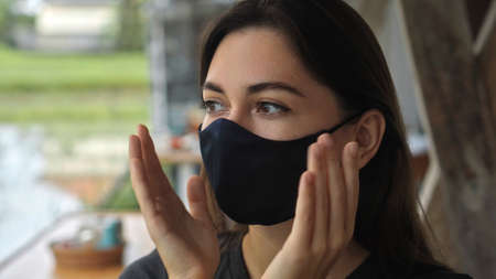 A young European brunette girl sits at a table in a public place and touches a soft black protective mask with her hands on her face 스톡 콘텐츠 - 163373585