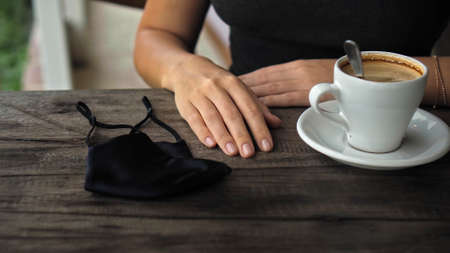 A young European girl sits at a table in a public place with a cup of coffee and nearby to her on a wooden table is a black protective mask 스톡 콘텐츠 - 163373588