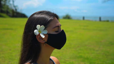 A young European brunette girl practices alone yoga in nature sitting on green grass in a lotus pose wearing a black protective mask on her face and a white flower behind her ear 스톡 콘텐츠