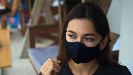 A young sad European brunette girl sits at a table in a public place on a black protective mask on her face Imagens