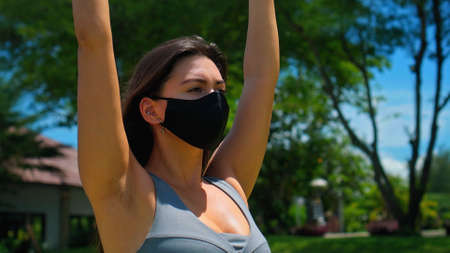 Young European brunette girl practices alone yoga in nature wearing a black protective mask on her face