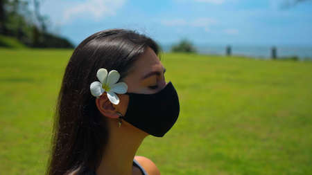 A young European brunette girl practices alone yoga in nature sitting on green grass in a lotus pose wearing a black protective mask on her face and a white flower behind her ear Imagens