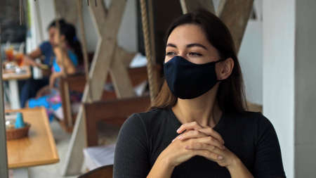 A young European brunette girl sits at a table in a public place on a black protective mask on her face Imagens