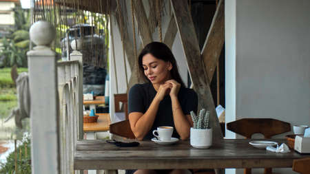 A young European girl sits at a table in a public place with a cup of coffee on a wooden table and looking on protective mask on a table Imagens