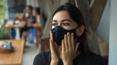 A young European brunette girl sits at a table in a public place and touches a soft black protective mask with her hands on her face Imagens