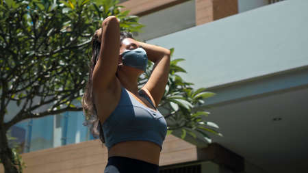 A young European brunette sports girl walks along an empty city street with green trees on the background alone in a gray protective mask on her face 스톡 콘텐츠 - 163015207