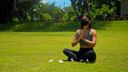 Young European brunette girl practices alone yoga in nature sitting on green grass in lotus pose wearing a black protective mask on her face 스톡 콘텐츠 - 163015209