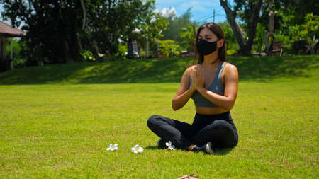 Young European brunette girl practices alone yoga in nature sitting on green grass in lotus pose wearing a black protective mask on her face