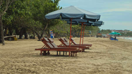 Rows of folded beach umbrellas and empty sunbeds on the beach, early morning Imagens