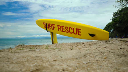 Yellow surfboard on beach with red text surf rescue emergency on a beach on a Bali island