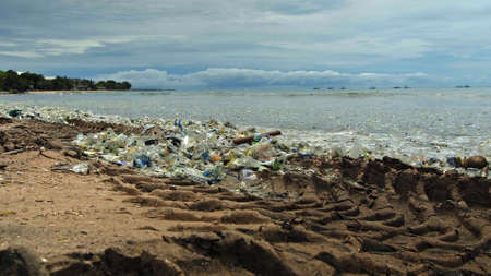 Beach pollution. 4K video of plastic garbage and other trash on sea beach. Ecological concept Imagens