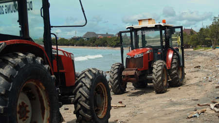 Kuta, Badung, Bali, Kuta Beach Indonesia - 4, January 2021: Tractor technic for cleaning the sea beach from garbage stands on the sand after throwing plastic garbage from the sea on the island of Bali in the city of Kuta