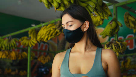 A young European girl in a black protective mask buys organic fruits in a store
