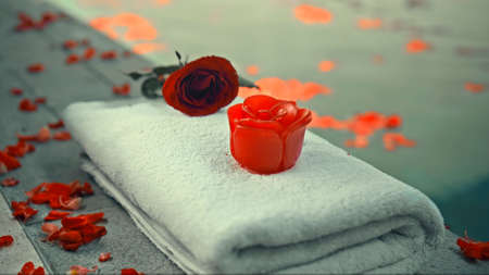 Red rose soap standing on a towel outside the pool with flower petals 스톡 콘텐츠
