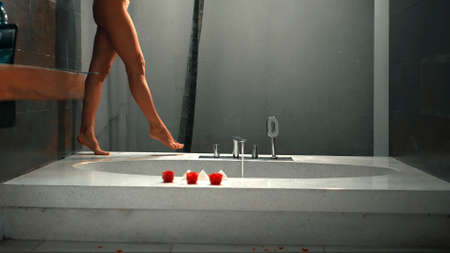 Legs of a young European girl walking around the bath on the bathroom with a crane close up