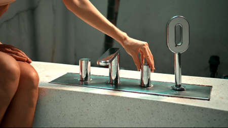 A young European girl sitting on a bath opens a tap with water in the bathroom with her hands 스톡 콘텐츠