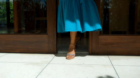 The legs of a young girl in a blue dress leaving the house in shoes opening wooden doors with glass windows
