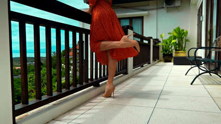 A young girl stands in the summer on a balcony in a red dress and heels lifting one leg 스톡 콘텐츠