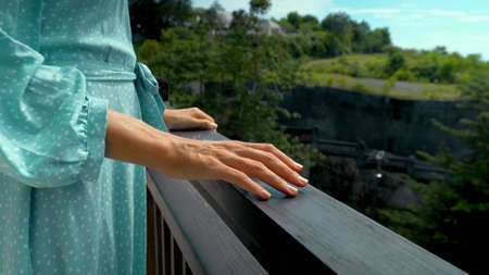 A young girl stands in the summer on a balcony in a blue dress clouding on a railing