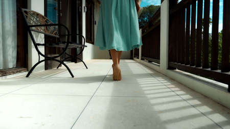 The legs of a young girl in a green dress walk along a balcony in high-heeled shoes