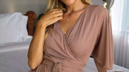 Young girl long-haired blonde touches a brown dress with her hand sitting on the roof in the house