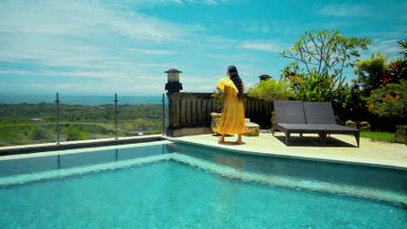 Young long-haired girl walking in the backyard with a green garden, pool with blue clean water and blue sky in a beautiful long yellow dress