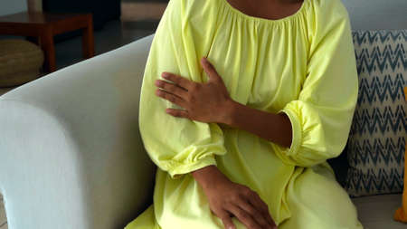 A young girl touches a yellow dress sitting on a couch in the house with her hand