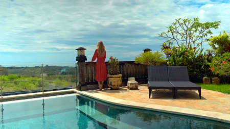 Young long-haired girl walking in the backyard with a green garden, pool with blue clean water and blue sky in a beautiful long red dress Banco de Imagens