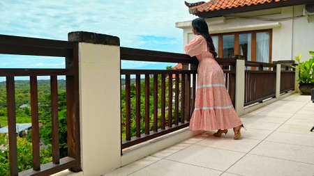 A young girl in a pink dress stands on a balcony overlooking the courtyard from the tropics with blue skies and clouds