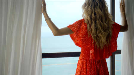 young European girl in a red dress with long hair, standing in the house behind the window and opening window curtains with her hands in different directions