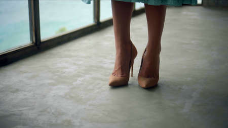 The legs of a young and beautiful European girl walking in the room