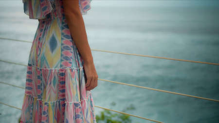 The young and beautiful European girl on a balcony overlooking the sea in a pink dress touches the railing with his hands