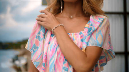 young and beautiful European girl with long hair in a pink dress touches a pendant hanging around her neck with her hands