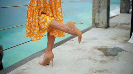 The legs of a young and beautiful European girl in shoes on a balcony overlooking the sea in a yellow dress and shoes with a long heel, lifted one leg 스톡 콘텐츠