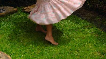 A young girl dances on grass in the backyard with a green garden in a beautiful long pink dress