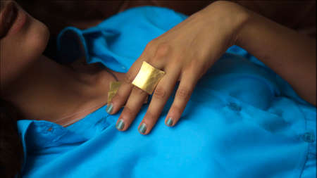 A young European girl in a blue dress lies on the couch and touches her hands with a golden ring