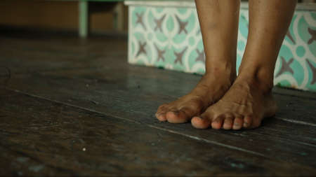 Legs of a young European girl walking along a wooden old floor