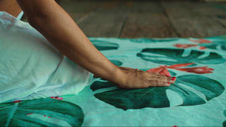 Hands of a young European girl touching a towel lying on a wooden floor 스톡 콘텐츠