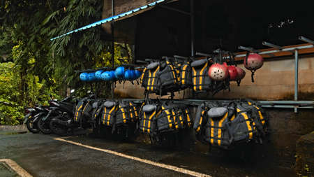 Black protective jackets with yellow lines and protective helmets to practice rafting hanging on a wall on the street Banco de Imagens