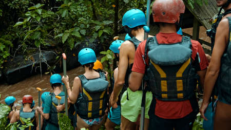 People descending stairs in black protective jackets with yellow lines and protective helmets for rafting and with weights