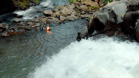 Picture of waterfall with rocks among tropical jungle with green plants trees and river. A girl lies at a waterfall after an unsuccessful jump from a waterfall Banco de Imagens