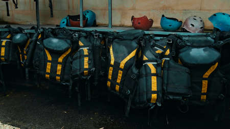 Black protective jackets with yellow lines to practice rafting hanging on a wall on the street