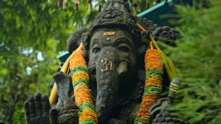 An old stone statue of Ganesha covered with moss with a wreath of yellow flowers on his neck standing on the street with green plants on the background