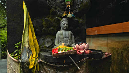 An old stone Budist statue sitting in a lotus pose covered with moss with a wreath of yellow flowers on its neck standing on the street with green plants on the background