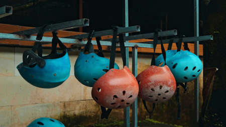 Colored protective helmets for the head to practice rafting hanging on the wall on the street Banco de Imagens