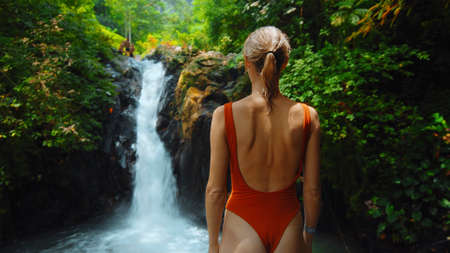 waterfall with rocks among tropical jungle with green plants and trees and water falling down into river with woman staying near the waterfall