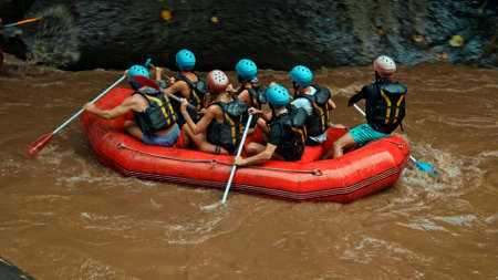 People sailing in black protective jackets with yellow lines and protective helmets on boats for rafting and with weights 스톡 콘텐츠