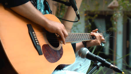 The young man plays hands and on a classic acoustic wooden guitar on the street using a microphone Banco de Imagens